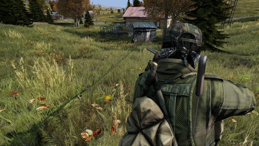 A man aims his gun down a grassy hill in DayZ, one of the best survival games.