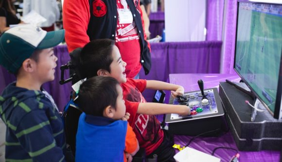 A child plays Fifa with an accessible joystick setup.