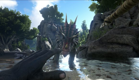 A man aims a spear at a dinosaur in one of the best dinosaur games, Ark: Survival Evolved