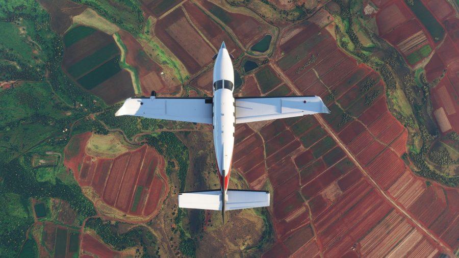 Light aircraft flying over fields in Microsoft Flight Simulator