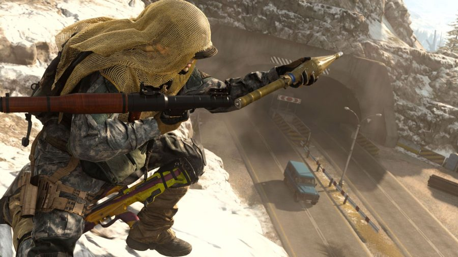 A soldier on a cliff with a cloak wrapped around his face arming a rocket propelled grenade. A teal car is driving on the road below.