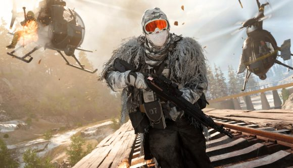 A man in a white ghillie suit and full face mask sprinting down train tracks with a rifle. Two choppers are behind him.