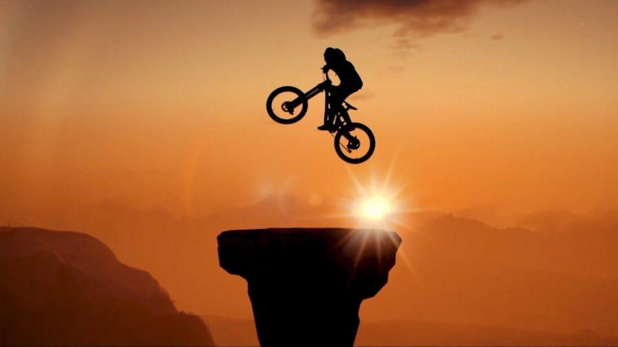 A cyclist hopping up above a rocky platform