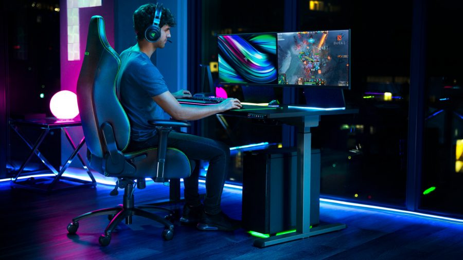 A man sits on the Razer Iskur gaming chair, playing Dota 2 with the logo on the screen for some reason