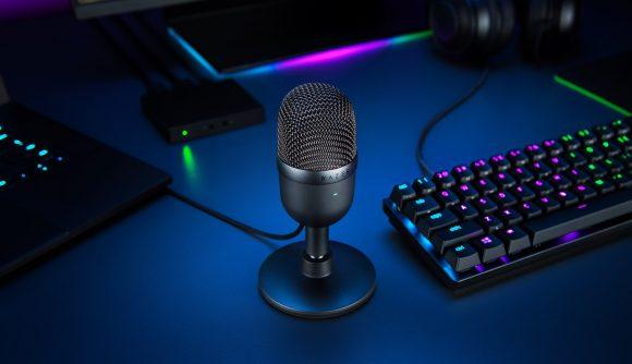 A black Razer Seiren Mini microphone sits next to an RGB gaming keyboard in a dimly lit room.