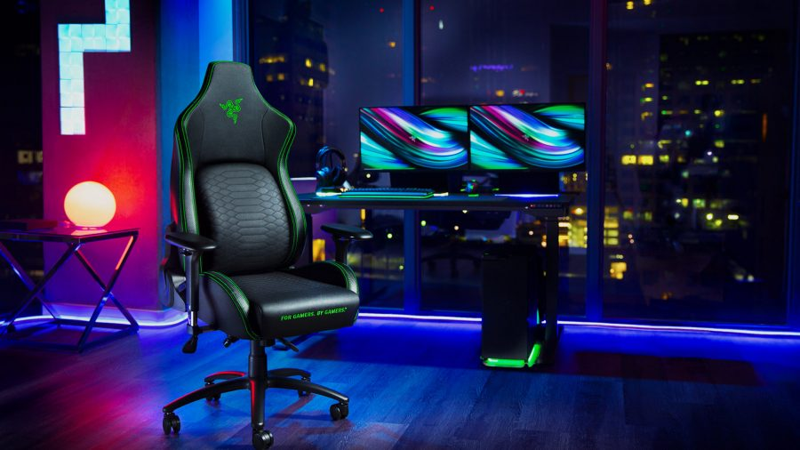 The Razer Iskur gaming chair sits in front of a dual monitor setup against RGB lighting