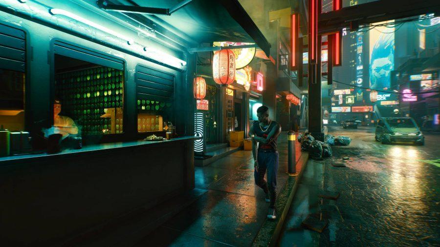 A man is walking past a shop.