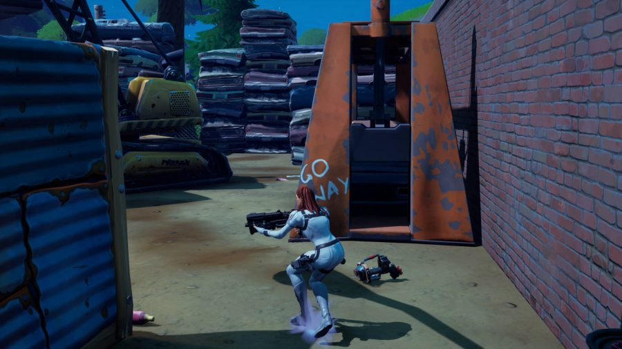 """Player walking close to one of the car parts in the junkyard outside of Dirty Docks in Fortnite. There is a machine that says """"Go Away"""" behind it."""