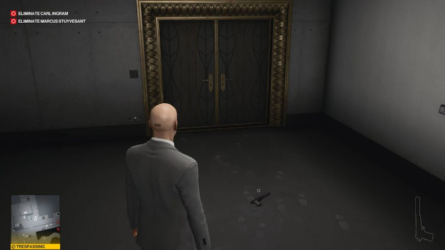 Agent 47 looks at the double doors