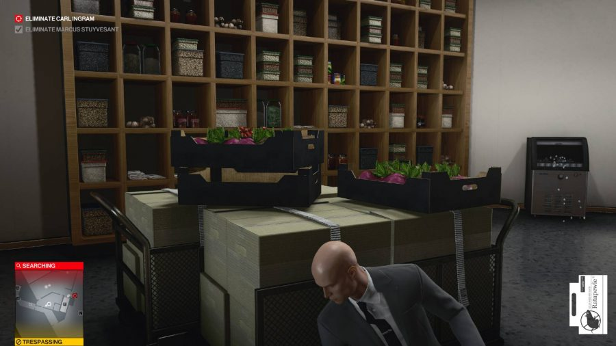Agent 47 is squatting behind a storage container in a pantry