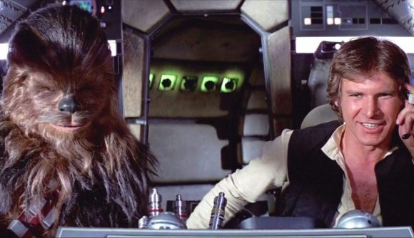 Han Solo and Chewbacca sitting in the bridge of the Millenium Falcon, Han is smiling