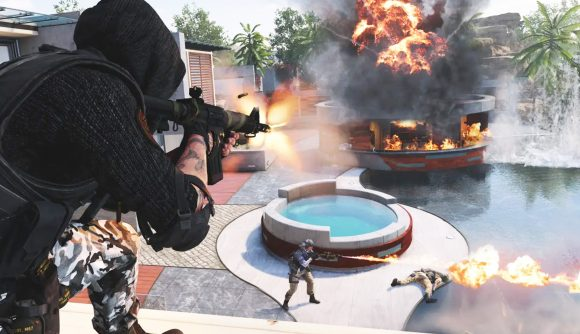 Two soldiers shooting at enemies in front of a burning building