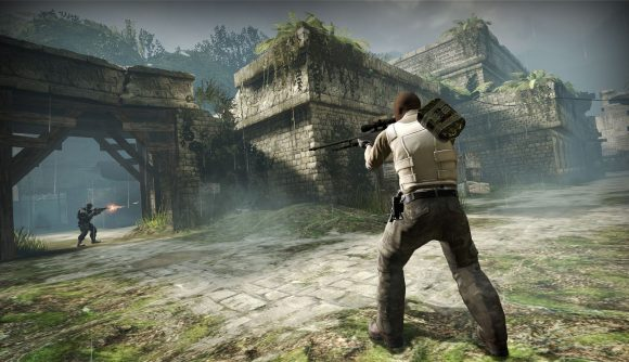 CS;GO's Aztec map, with ancient stonework, a crumbling bridge, and an armed character shooting aiming a rifle into the distance