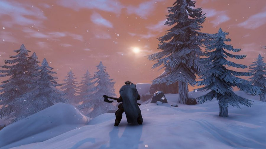 A Viking stands on top of a snowy hill during sunrise, surrounded by trees that have been covered