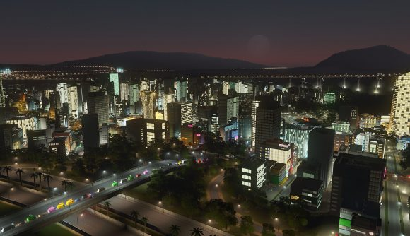 Looking over a city, lit up at night, from just over a neighbouring highway