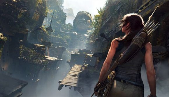 Shot of Lara Croft, on a ledge in an overgrown jungle temple, staring at a stone face, facing broken wooden bridges