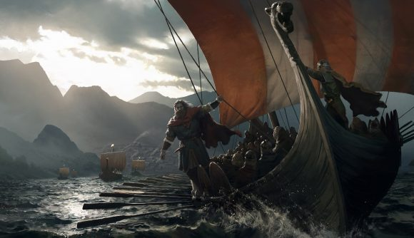 A man in medieval garb stands on the side of a viking longship at sea, mountains behind him