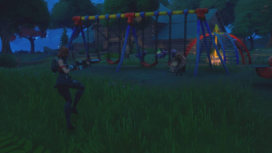 The player is hunting a boar, one of the animals in Fortnite, in a children's playground.