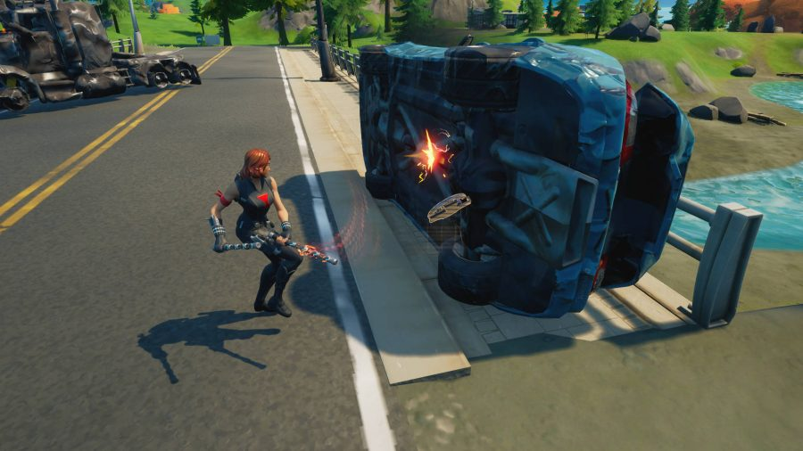 The player is hacking away at an flipped car to harvest mechanical parts for crafting in Fortnite. An exploded lorry is near.