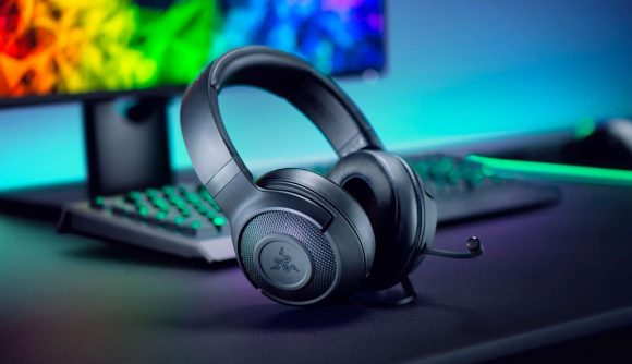 Razer headset placed on a desk behind an array of other RGB-clad Razer products