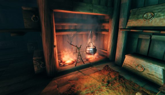 A cauldron and cooking station over a fire pit in Valheim