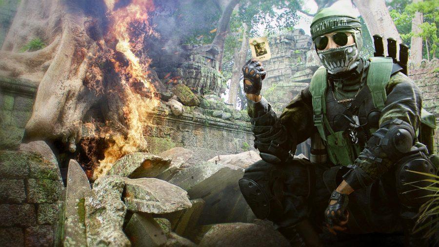 Kapano Naga Vang holding a playing card while a tree burns next to him