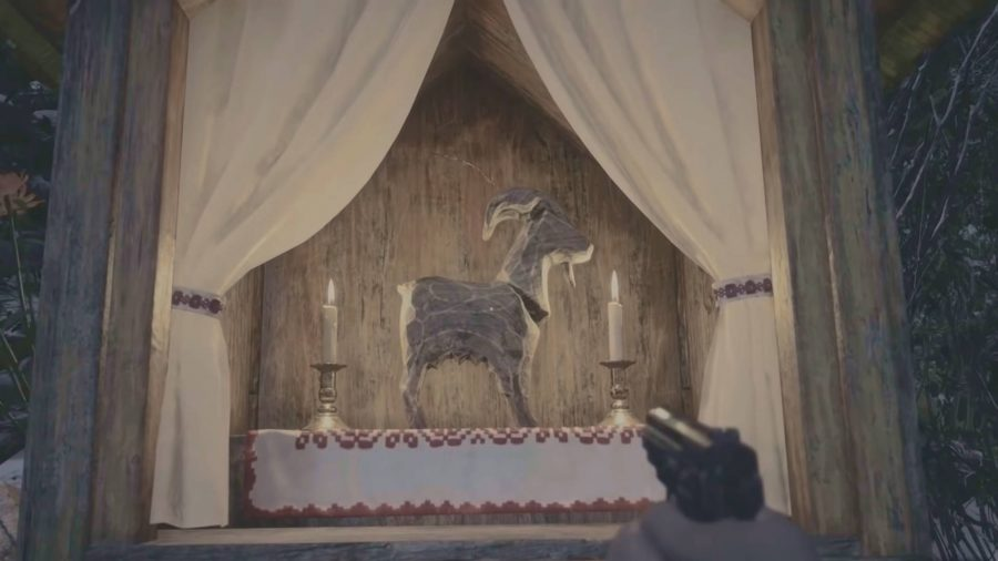 One of the many goats of warding in Resident Evil Village. This one is in a shrine with candles either side.