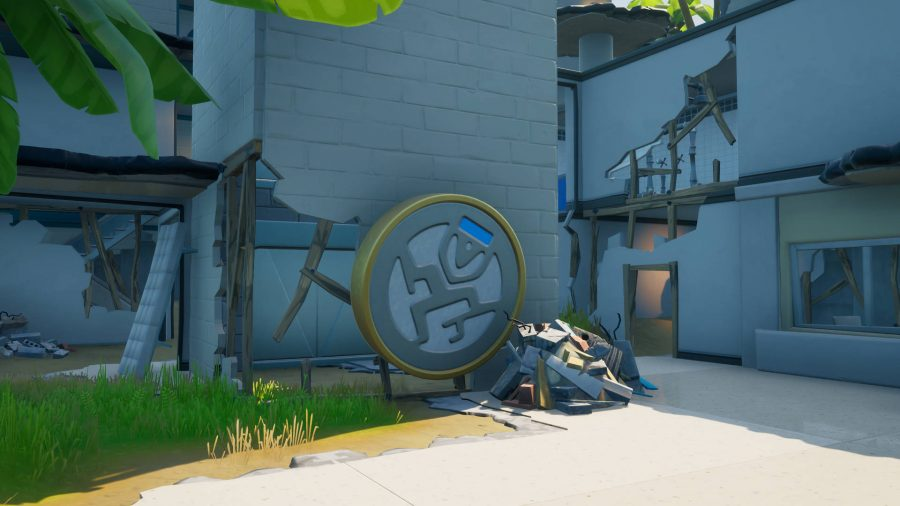 The Fortnite Ghost Ruins has an emblem dislodged from the wall among the dilapidated walls.
