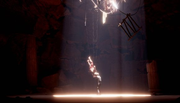 A soldier dangling on a rope in a dark underground cave