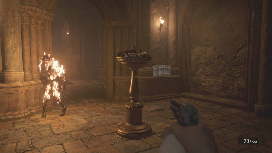 Inside the Resident Evil Village riverbank treasure house, an enemy pursues Ethan whilst on fire. An unlit torch is nearby.