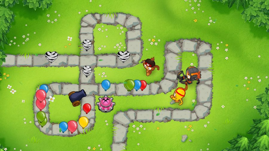 Balloons make their way along a stone path in a grassy field, with turrets on