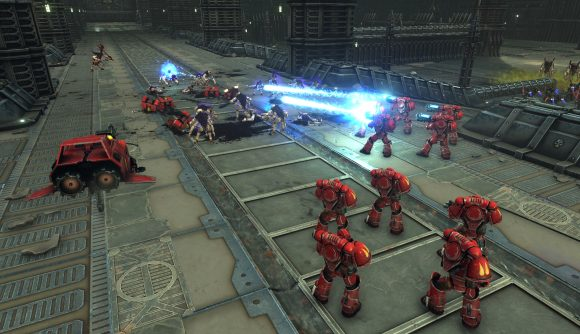 a squad of space marines fires plasma weapons at advancing tyranids