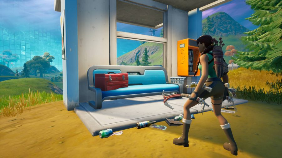 Lara is looking at a red toolbox, which has nuts 'n' bolts inside for use with crafting in Fortnite.