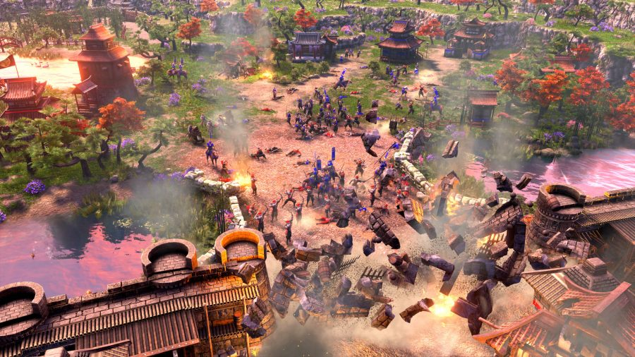 A castle under siege in Age of Empires 3, with the main gates blowing open from an explosion