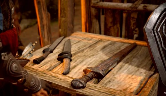 A crude one-handed sword rests on a worktable in Assassin's Creed Valhalla