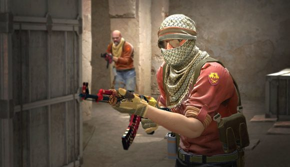 A CS:GO character with a red shirt and machine gun in a dusty alley