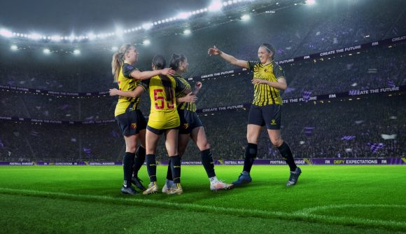 Women football players embrace on the pitch in Football Manager promotional art.