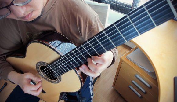 Cecil Chau, aka GuitarSVD, plays an arrangement on his classical nylon-string guitar at his desk.