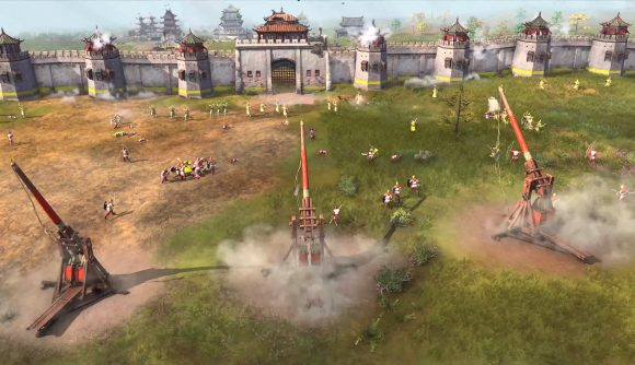 A line of trebuchets firing at a castle wall in rts game age of empires 4