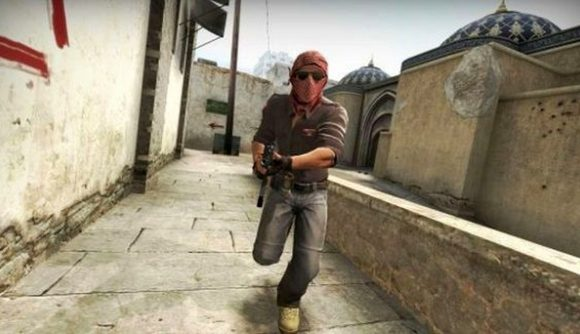 A CS:GO character running at the camera with a rifle in the Mirage map