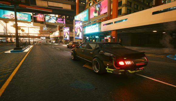 V's car heads down a Night City street at dusk in Cyberpunk 2077.