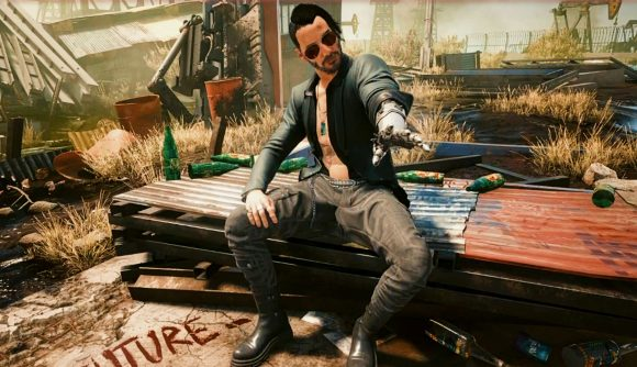 Johnny Silverhand extends his left hand while wears an alternative costume and undercut hairstyle in Cyberpunk 2077.