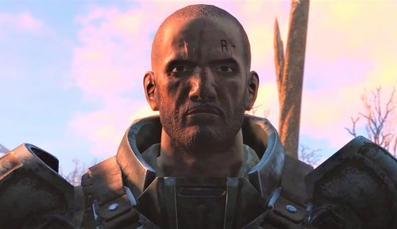 A cropped-haired man in chunky metal armour looks beyond the camera with a sunset behind