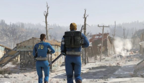 Two vault dwellers walk down a road that leads through a ruined town in Appalachia in Fallout 76