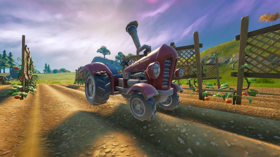 A shiny red tractor parked on a field in Fortnite.