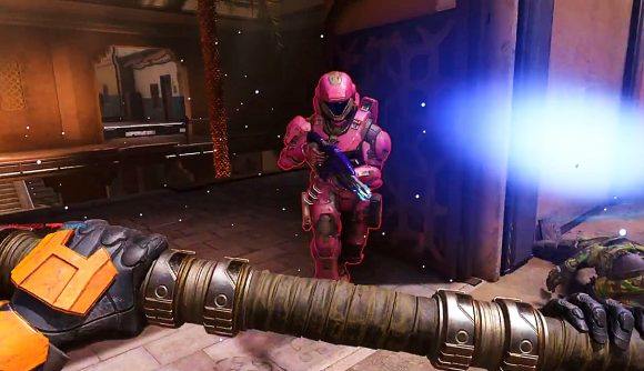 A Halo Spartan clad in pink armour runs forward, in view of another Spartan holding a large hammer.