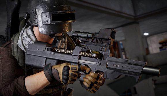 A character wearing a welding helmet and combat gloves shoulders a P90 submachine gun in PUBG: Battlegrounds.