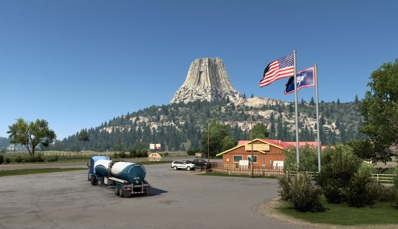 A number of vehicles parked outside a Wyoming gift shop near a mountain in the new American Truck Simulator DLC