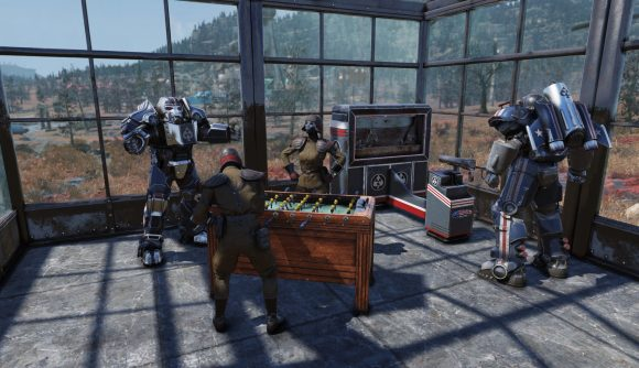 Members of the Brotherhood of Steel play foosball and arcade games in a brightly lit room looking out across the wilderness in Fallout 76