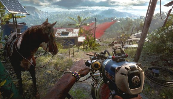 A screenshot from Far Cry 6 from the player character's perspective looking down over a valley with aeroplanes flying overhead